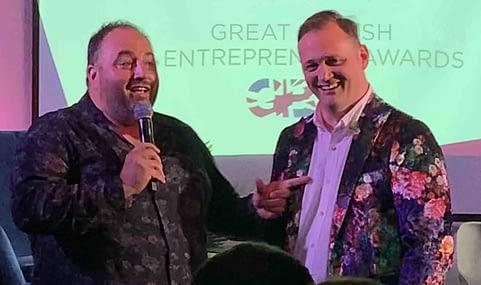 Welsh opera singer Wynne Evans and popcorn founder Simon Washbrook, in a floral jacket, speaking at a Great British Entrepreneur Awards event