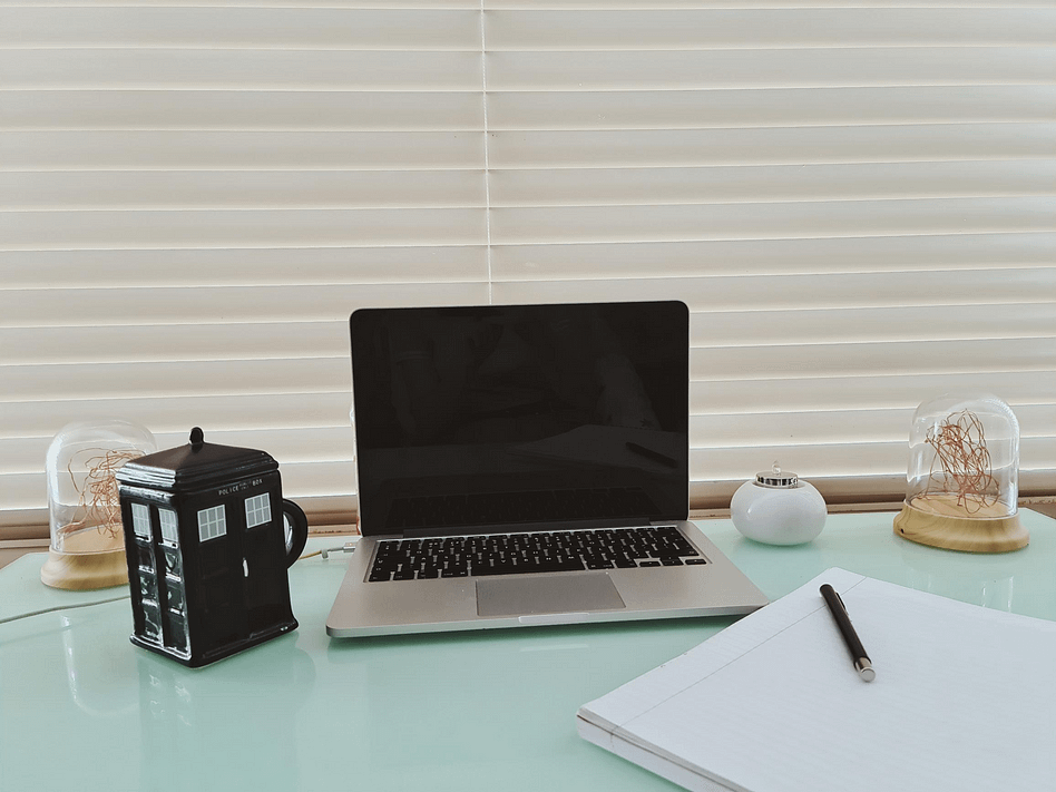 Setup of a Macbook, Doctor Who TARDIS mug and notebook on a light green desk
